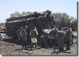 Afghan police look at fuel tanker destroyed by NATO jets