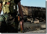 Afghan soldier near one of two fuel tankers bombed by NATO airstrike in Kunduz