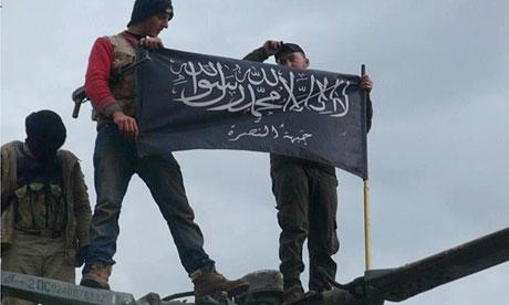 Al-Qaida affiliated Jabhat al-Nusra rebels hold up their flag after capturing Taftanaz air base