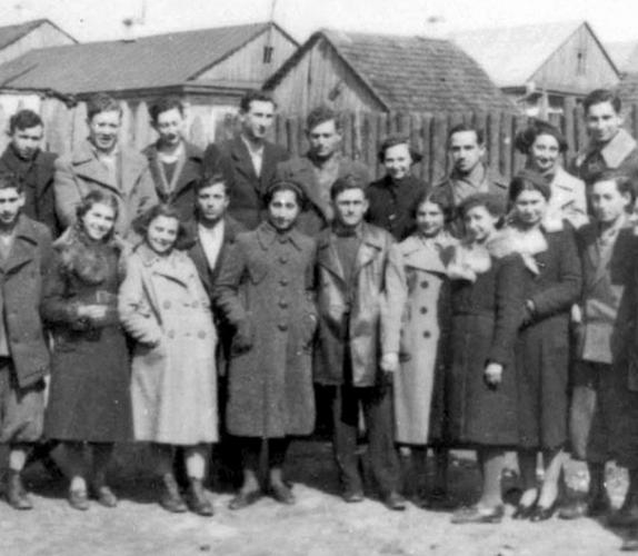Jovenes judíos sonrientes de Mirfrente a sus casas de madera