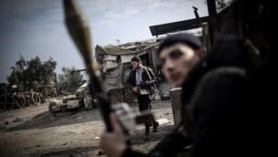 Combatientes del Ejército Libre de Siria sostienen sus armas durante fuertes enfrentamientos con las fuerzas del gobierno en Aleppo, Siria, en Domingo, 20 de enero 2013 (Foto: AP / Andoni Lubaki).