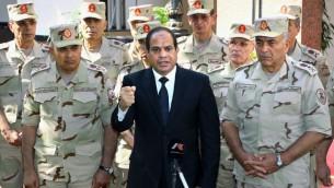 El presidente egipcio, Abdel-Fattah el-Sissi, centro, habla delante de la televisión estatal antes de un funeral militar de 30 soldados muertos en un asalto en la península del Sinaí, como él está con los comandantes del ejército en El Cairo, Egipto, el sábado, 25 de octubre 2014 (Foto: AP / MENA)