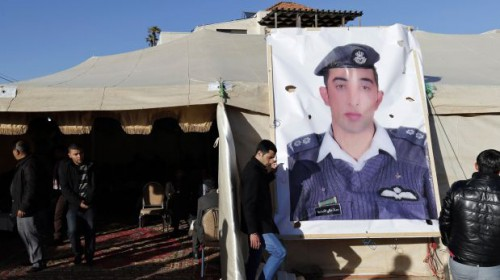 Relatives of Islamic State captive Jordanian pilot Muath al-Kasaesbeh place a poster of him in front of their new gathering headquarters in Amman