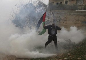 Palestinian protester holding a Palestinian flag runs away from tear gas fired by Israeli soldiers during clashes following a protest in the West Bank village of Kofr Qadom near Nablus