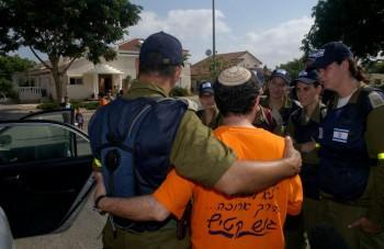 Un soldado visto consolando a un residente durante la evacuación de la comunidad israelí Ganei Tal, de agosto de 2005. (Foto: IDF)