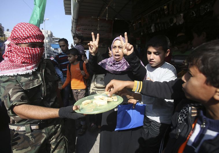 A masked Palestinian distributes sweets as he celebrates with others an attack on a Jerusalem synagogue, in Rafah in the southern Gaza Strip November 18, 2014.  Two Palestinians armed with a meat cleaver and a gun killed four people in a Jerusalem synagogue on Tuesday before being shot dead by police, the deadliest such incident in six years in the holy city amid a surge in religious conflict. REUTERS/Ibraheem Abu Mustafa (GAZA - Tags: POLITICS CIVIL UNREST)