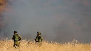 Dos soldados de las FDI de pie en medio de un gran incendio asola cerca de Kfar, causado por misiles disparados desde el lado sirio de la frontera sirio-israelí y golpear áreas abiertas en los Altos del Golán en el norte de Israel el 20 de agosto de 2015 (Basilea Awidat / Flash90)