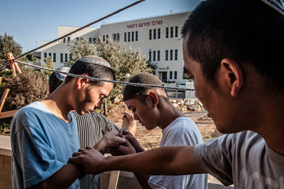 When building the sukkah, Yakkov wounded one of his fingers by the wooden spikes from the contruction materials. Shefi and Fei were inspecting his wound.