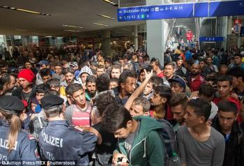 """Reclamaciones: El falsificador dijeron MailOnline que """"todo el mundo quiere ser sirio ahora - porque ahora todo el mundo da la bienvenida a los sirios. Hay palestinos, egipcios, iraquíes, la gente de todo el mundo árabe están fingiendo ser sirio para que puedan tener una nueva vida en Europa ». Migrantes foto aparecen en la estación de Salzburgo, Austria el martes"""