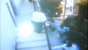 Esta captura de pantalla de una cámara de circuito cerrado de televisión muestra Faiz Abu Hamadiah, izquierda, apoyado en una barandilla, y los estudiantes de yeshiva judío a quien salvó de una turba palestina disturbios (captura de pantalla: Canal 2)