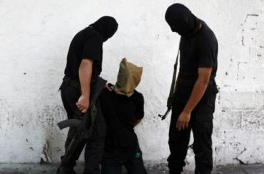A Hamas militant grabs a Palestinian suspected of collaborating with Israel, before being executed in Gaza City August 22, 2014. REUTERS/Stringer