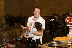 Un israelí lleva a un niño herido en un ataque terrorista en Jerusalén. (Yonatan Sindel / Flash90)