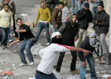 Palestinian protestors throw stones at Israeli security forces during a demonstration against the Israeli air strikes on Gaza in the centre of the West Bank city of Hebron on December 27, 2008. Palestinians threw stones at Israeli forces who responded with tear gas during a Palestinian demonstration in Hebron today protesting the Israeli blitz of Hamas targets in the Gaza Strip that killed at least 195 people. Israel sent a wave of air strikes against targets in the besieged enclave in retaliation for ongoing rocket fire, officials said. AFP PHOTO/HAZEM BADER