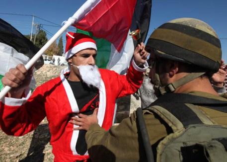 HEB02 AL MASARA (CISJORDANIA) 23/12/2011.- Un soldado israelí se enfrenta a un palestino vestido de Papá Noel durante una protesta contra el muro de separación israelí en el pueblo de Al Masara, Cisjordania, hoy viernes 23 de diciembre de 2011. EFE/ABED AL HASHLAMOUN