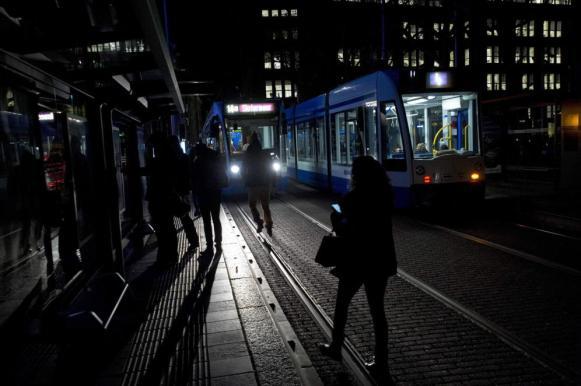 Un grupo de personas espera un transporte en la oscuridad, en Ámstedam