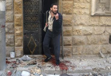 A man reacts as he stands on blood stains at a site hit by airstrikes in the rebel held area of Aleppo's al-Fardous district