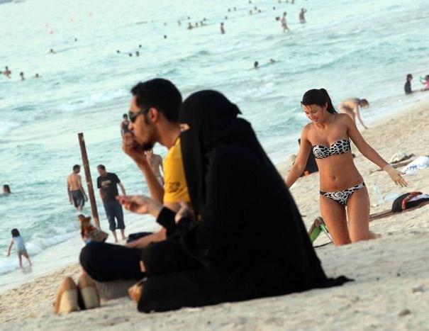 329560_contraste-entre-la-tenue-d-une-femme-emiratie-et-une-occidentale-sur-une-plage-de-dubai-le-21-mai-2012